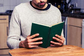 Young man reading in his kitchen — Stock Photo