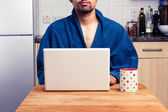 Man in robe working from home — Stock Photo