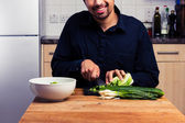 Happy man chopping vegetables — Stock fotografie