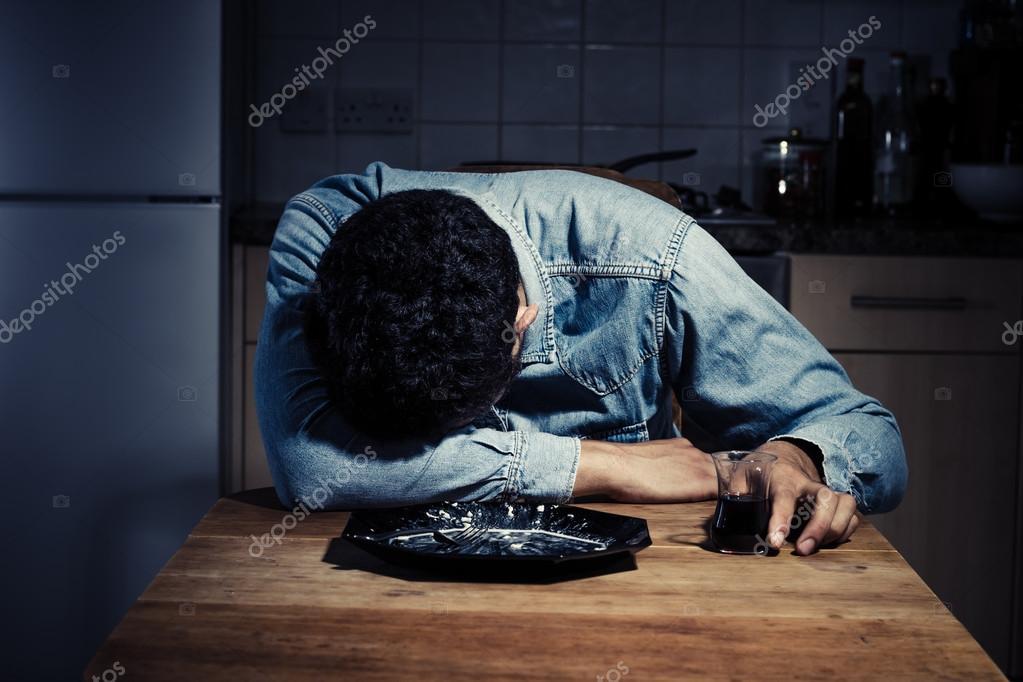 晚餐后喝酒的悲伤和孤独的男人