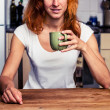 Woman drinking from cup in her kitchen — Stock Photo