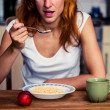 Stock Photo: Young woman having cereal and fruit for breakfast