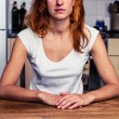 Calm woman sitting in her kitchen — Stock Photo