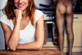 Happy woman waiting for her naked boyfriend to cook for her — Stock Photo