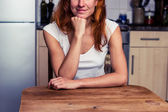 Happy woman relaxing in her kitchen — Stock Photo
