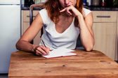 Thoughtful woman writing in her kitchen — Stock Photo