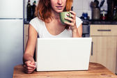 Woman drinking coffee and working on laptop — Stock Photo