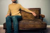 Joven en sofá ofrece un asiento — Foto de Stock