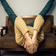 Tired young man is upside down on old sofa — Stock Photo
