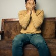 Upset young man sitting on old sofa — Stock Photo #30953041