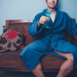 Young playboy in dressing gown toasting with cocktail — Stock Photo