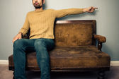 Young man on sofa pointing right — Stock Photo