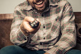 Happy man watching television and changing the channel — Stock Photo