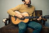 Giovane uomo sul vecchio divano è suonare la chitarra — Foto Stock