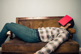 Man sleeping on old sofa with book covering his face — Stockfoto