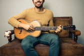 Happy young man playing guitar on old sofa — Stock Photo