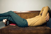 Young man sleeping on old sofa — Stock Photo