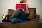 Young man reading on old sofa — Stock Photo