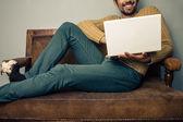 Jeune homme avec portable sur vieux sofa souriant — Photo