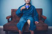 Young man in robe drinking coffee on sofa — ストック写真