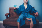 Happy young man in dressing gown drinking martini — Stock Photo