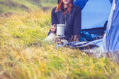 Woman camping and cooking with portable gas stove — Stock Photo