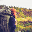 Woman with backpack watching fellow hill walkers in the distance — Stock Photo