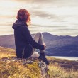 Woman admiring sunset from mountain top — Stock Photo