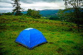 Tent pitched on a green hillside — Foto de Stock