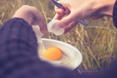 Woman cracking an egg on portable camping stove — Stock Photo