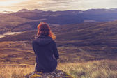 женщина, сидя на вершине горы и созерцая — Стоковое фото