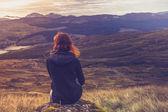 žena sedí na vrcholu hory a uvažuje o — Stock fotografie