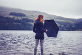 Young woman with an umbrella standing in lake — Stock Photo