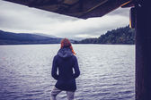 マリーナに立っていると見ている湖の女性 — ストック写真