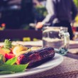 Salad and sausage on sunny day with man in background — Stock Photo