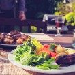 Salad, sausage and chicken at family barbecue — Stock Photo