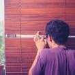 Young man peeping out through venetian blinds — Stock Photo