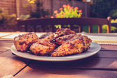 Plate of chicken outdoors at a barbecue — Stock Photo