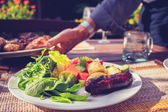 Man setting table at outdoors barbecue — Stock Photo