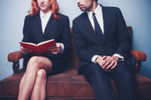 Businessman looking at businesswoman's book — Stock Photo