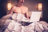 年轻男人是坐在床上,看着笔记本上色情 — 图库照片