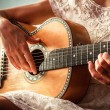 Young woman playing guitar indoors on sunny day — Stock Photo