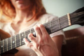 Close up on young woman's hand playing guitar — Stock Photo