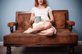 Young woman in summer dress sitting on old sofa drinking tea — Stock Photo