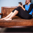 Young woman sitting on sofa reading digital book — Stock Photo