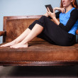 Young woman sitting on sofa reading on a tablet — Stock Photo