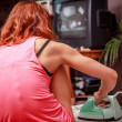 Young woman ironing her clothes at home and watching TV — Stock Photo #33170627