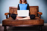 Calm young woman sitting on sofa with legs crossed using laptop — Stock Photo