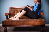 Jovem mulher sentada no sofá, usando um tablet — Fotografia Stock