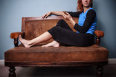Young woman sitting on old antique sofa holding her phone — Stock Photo